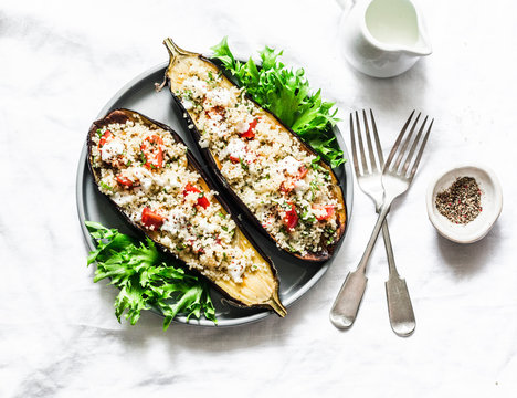 Baked eggplant stuffed with couscous, tomatoes, cilantro with yogurt sauce on a light background, top view