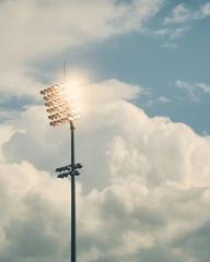 Stadium floodlights against cloudy sky