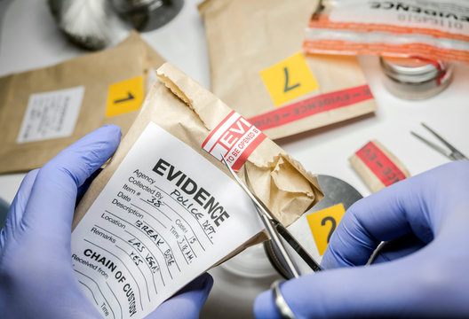 Scientific police opens with scissors a bag of evidence of a crime in scientific laboratory