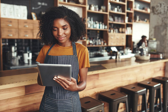 Successful small business owner using digital tablet in her cafe