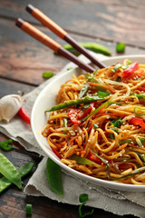 Chow mein, noodles and vegetables dish with wooden chopsticks