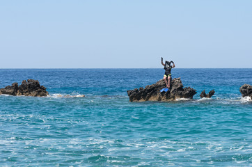 Female pirate diver captures the island in the faraway sea and announces free economic zone - a joke. Young woman, frogman, corsair with Jolly Roger flag. Seascape with human on sunny day, vacation.