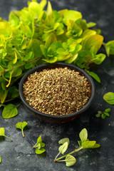 Fresh and dried oregano in bowl. on black rustic table