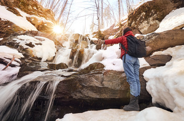 Girl stands arms up in front of the winter waterfall and orange sun