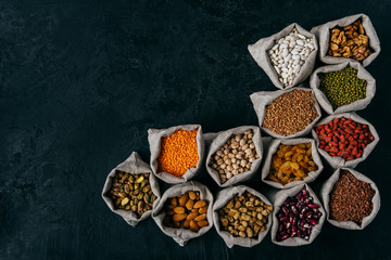 Horizontal shot of little sacks filled with almonds, walnuts, raisins, garbanzo, kidney bean, red goji, isolated over dark background, blank space for your advert