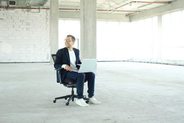 Young businessman with laptop in the big hall