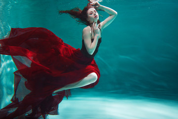 beautiful young woman in a red dress swims under water