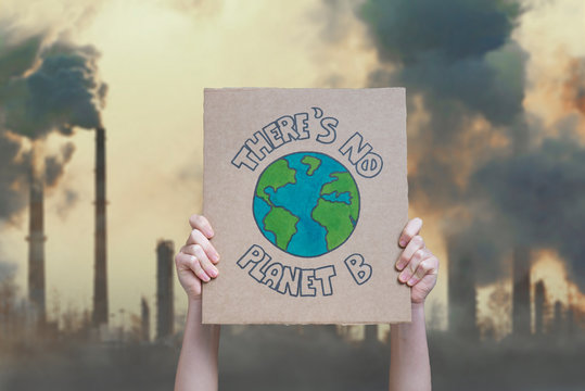 Climate change manifestation poster on an industrial fossil fuel burning background: there is no planet b