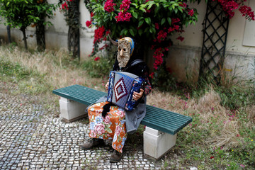 """A member of the """"Entrudo das Aldeias do Xisto"""" folk group poses for a photo before the parade of the 14th International Festival of the Iberian Mask in Lisbon"""