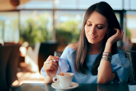 Woman Drinking Coffee by Herself in a Restaurant