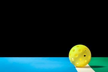 Small Yellow Pickleball with large background Yellow Pickleball on the boundry line of pickleball court and large background that can easily be remove and replaced.  Blue court area and green out of p