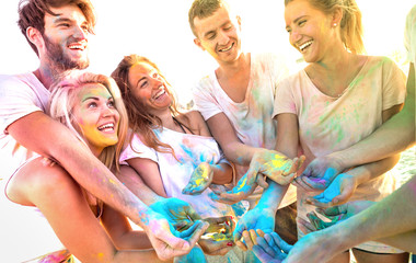 Young friends having fun at beach party on holi colors festival - Happy people playing together...