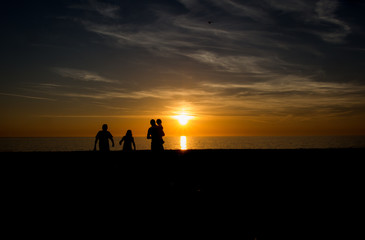 Family walking into sunset on the beach