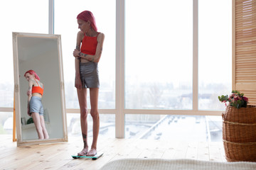 Woman with tattoos checking her body weight looking into mirror