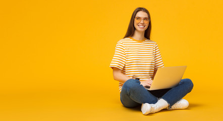 Horizontal banner of young smiling woman sitting on floor holding laptop, isolated on yellow...