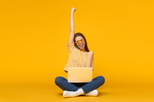 She is a winner! Excited young female with laptop isolated on yellow background