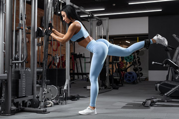 Foto op Plexiglas Ezel Fitness woman doing exercise for glutes, cable kickbacks. Athletic girl workout at the gym. Beautiful butt in leggings