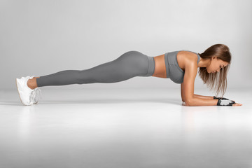 Fitness woman doing planking exercise, workout. Slim athletic girl training, isolated on the gray background. Fototapete