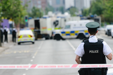 Police officer stands guard at a Police cordon point while army ATOs deal with a suspect bomb.