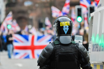 A poilce officer dressed in riot gear watches a crowd carrying Union Flags.