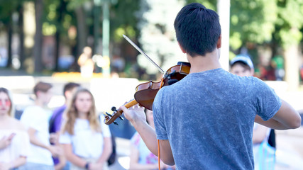 guy plays violin for street people. classical music lovers.