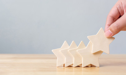 Hand putting wooden five star shape on table. The best excellent business services rating customer...