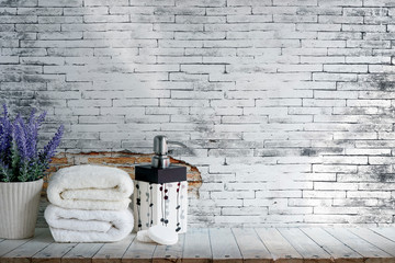 Mockup folded towel with soap and houseplant on wooden table with old brick wall.