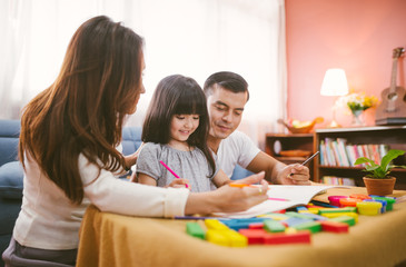 Portrait of happy family daughter girl is learning drawing book together with parent