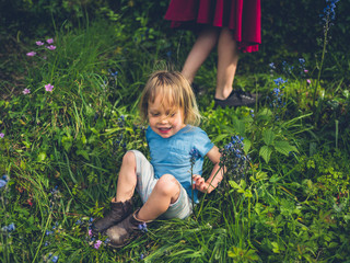 Little toddler sitting in garden with bluebells