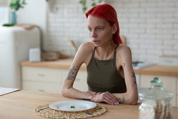 Anorexic woman looking awful sitting near plate with three peas