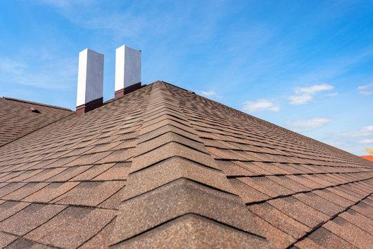 Asphalt tile roof with chimney on new home under construction