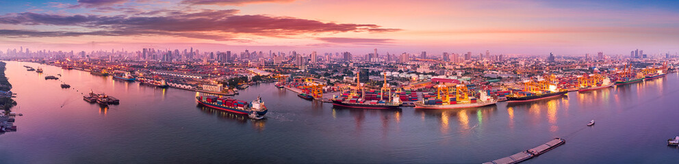 Wall Mural - Aerial panoramic view of Logistics and transportation of Container Cargo ship and Cargo plane with working crane bridge in shipyard at sunrise, logistic import export and transport industry background