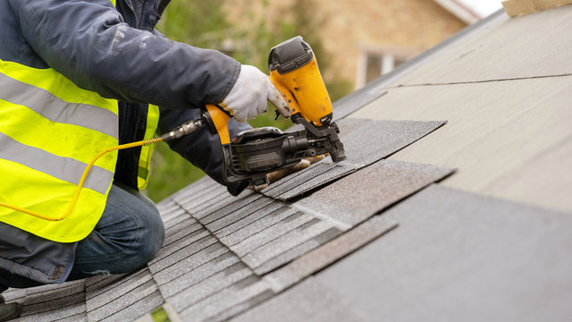 Workman using pneumatic nail gun install tile on roof of new house under construction