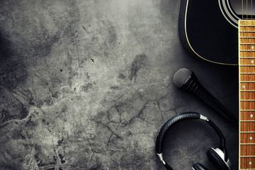 Guitar and accessories on a stone background. Desk musician, headphones, microphone.