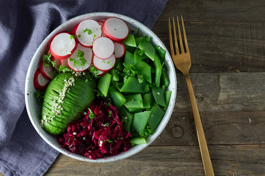 Top view of healthy Buddha Bowl salad with flat green beans, pink radishes, half avocado sliced, shredded cabbage and beets, hemp seeds, parsley in a white pottery bowl on rustic wooden table