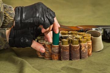 hands of huntsman fill a bandolier of hunting ammo