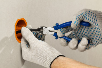 hands with cutter clears the insulation of wires