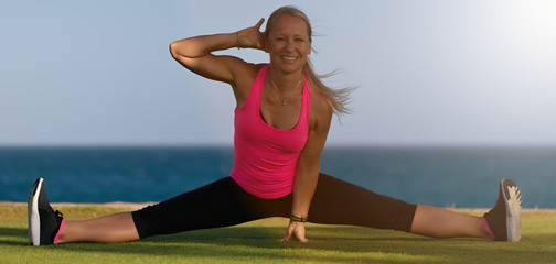 Female gymnast in sportswear, does leg split, sits on grass on ocean coast, poses in yoga, has workout exercises, stretches legs, demonstrates splits, likes fitness.