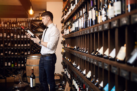 man reading the content of the bottle of wine. close up side view photo. the taste preference. elegant wine
