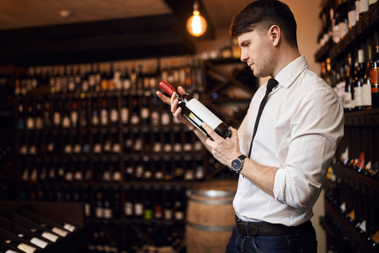 wine seller holding a bottle of wine at workplace. close up side view photo.man attend professional courses to become semmilier. education concept