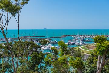 Blick über einen Yacht-Hafen hinaus aufs offene, türkis-farbene Meer