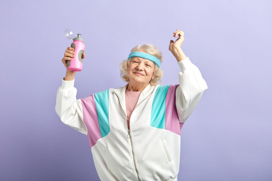 Water Balance in Older Persons. Senior woman in sportswear with water bottle smiling and dancing isolated on purple. Age Concept, Sport Recreation and Water Balance.
