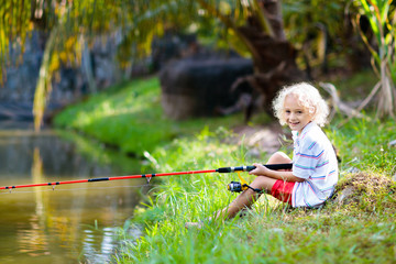 Boy fishing. Child with rod catching fish in river