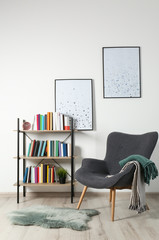 Comfortable armchair and shelving unit with different books near wall in room