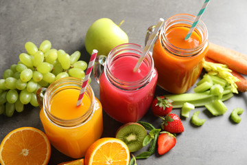 Mason jars with different juices and fresh ingredients on table