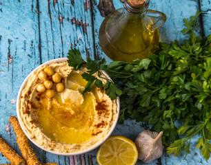 Humus w misce. Obok oliwa, cytryna, czosnek i pietruszka.