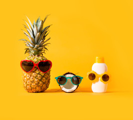 Pineapple and coconut wearing sunglasses with sunblock on a solid background