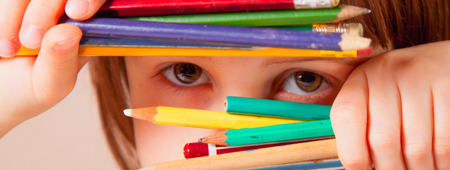 Humorous photo of great artist. Close up portrait of cute little child girl with colored pencils.
