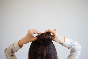 A young woman with brown hair ties her hair into a bun, viewed from the rear. Tutorial photo of simple hairstyle pinned half updo for long hair