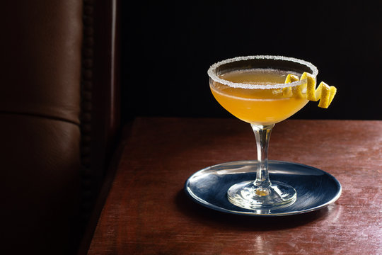 Sidecar Cocktail Served Up with Sugared Rim in Dark Luxurious Bar with Copy Space
